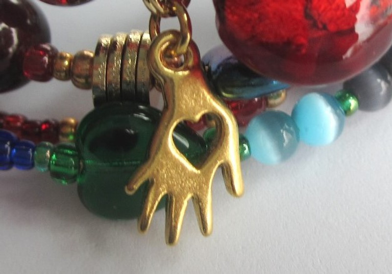 """A heart in hand charm symbolizes the aria """"O Dolce Mani"""" in which Mario expresses his amazement that such sweet and delicate hands could have killed Scarpia for his sake."""