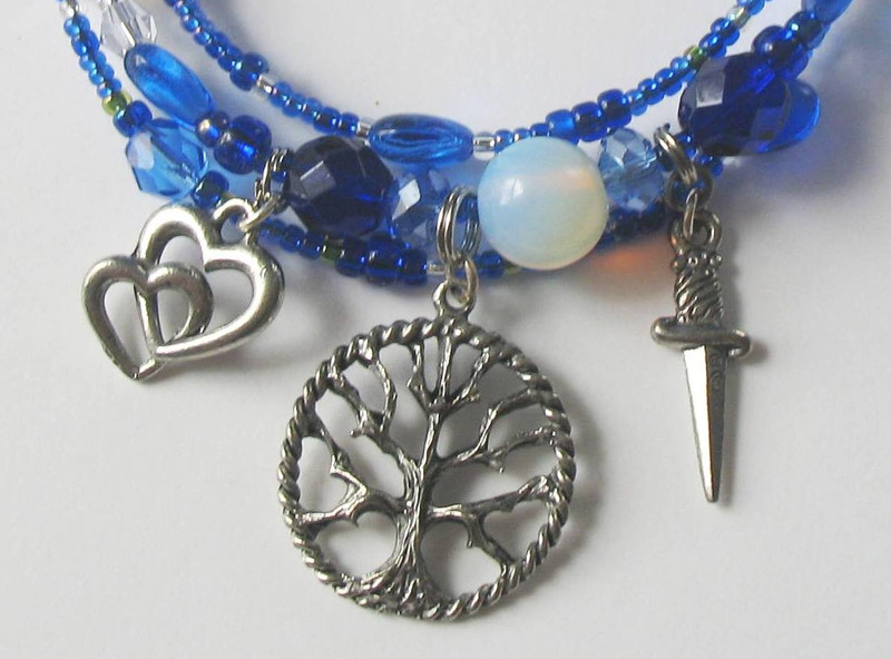 Entwined hearts represent Siegmund and Sieglinde. The tree symbolizes the ash tree growing through Hunding's house, the sword charm is Nothung.