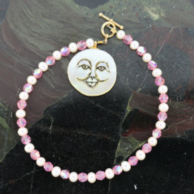 "Bracelet. Moon face carved on mother of pearl By Paul Grussenmeyer.  7.5"" length. Toggle clasp."