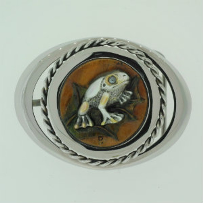 "Belt Buckle. Stainless Steel. Frog carved on mother-of-pearl, mounted on carved Tigerwood by Paul Grussenmeyer. Hematite eye. 3' X 2.38""."