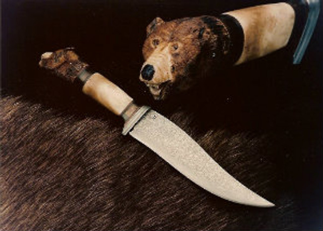 """Grizzly Bear carved on India Sambar crown stag by Paul Grussenmeyer. Citrine eyes. 7"""" forged damascus blade and guard made by master bladesmith James Porter. Handle composed of leather washers, amber, oosic, and Sambar stag. 12.5"""" overall."""
