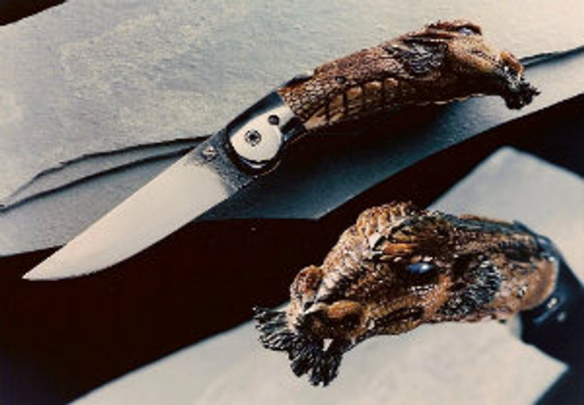 """""""Equis"""". A horse-headed dragon carved on a mule deer crown stag friction folding knife forged by Wendell Fox. Opal eyes with painted pupils, 3.38"""" 1095 steel blade, differentially tempered, etched, file worked and scrolled blade with stop stud, 416 stainless steel bolsters, brass liners, 1095 steel backliner file worked inside and out. 7.75"""" opened length."""