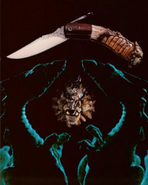 """""""Groper"""". Carved goblin friction folding knife forged by Wendell Fox with Paul Grussenmeyer's carved menacing goblin figure embellishment. Opal eyes with painted pupils, 3.25"""" blade of 1095 steel, differentially tempered, file worked blade and backliner (inside and out), brass liners, walnut bolsters, 7.75"""" opened length."""