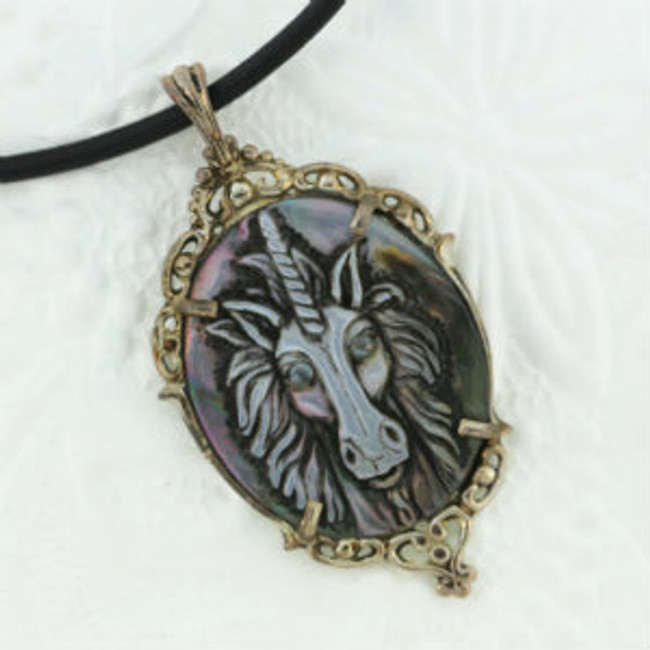 """A black pearl unicorn with aquamarine eyes carved by Paul Grussenmeyer. Mounted on an antiqued sterling silver frame, Greek letter cord. 16.5"""""""
