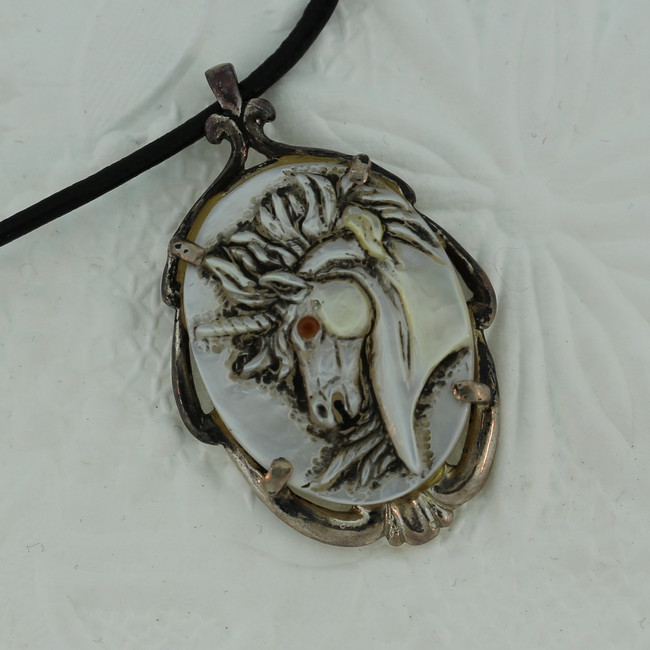 """Unicorn profile carved on mother-of-pearl with a ruby eye, mounted on an antiqued sterling silver frame by Paul Grussenmeyer. 16"""" Greek leather cord."""
