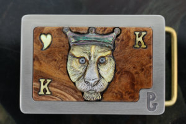 """King of Hearts"" belt buckle. Carved gold lip mother-of-pearl lion face, heart, and K's with abalone crown and hematite eyes by Paul Grussenmeyer. Set in burl wood and mounted in Paul's signature series stainless steel belt buckle."