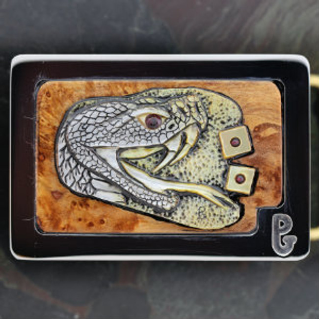 "Belt buckle with carved gold lip mother-of-pearl rattle snake head and ""Snake Eyes"" roll of the dice. Set in burl wood and mounted in Paul's signature series stainless steel belt buckle."