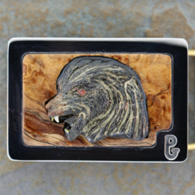 Belt buckle with carved Picasso marble wolf by Paul Grussenmeyer. Pearl teeth, garnet eye, set in burl wood and mounted in Paul's signature stainless steel belt buckle.