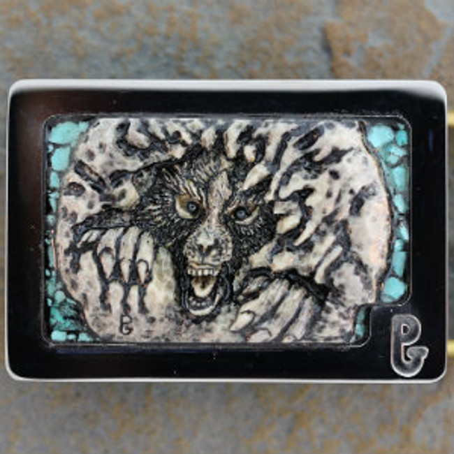 Belt buckle with carved American Moose stag (antler) wolf clawing through rock by Paul Grussenmeyer. Hematite eyes and turquoise accents. Mounted in Paul's signature series stainless steel belt buckle.