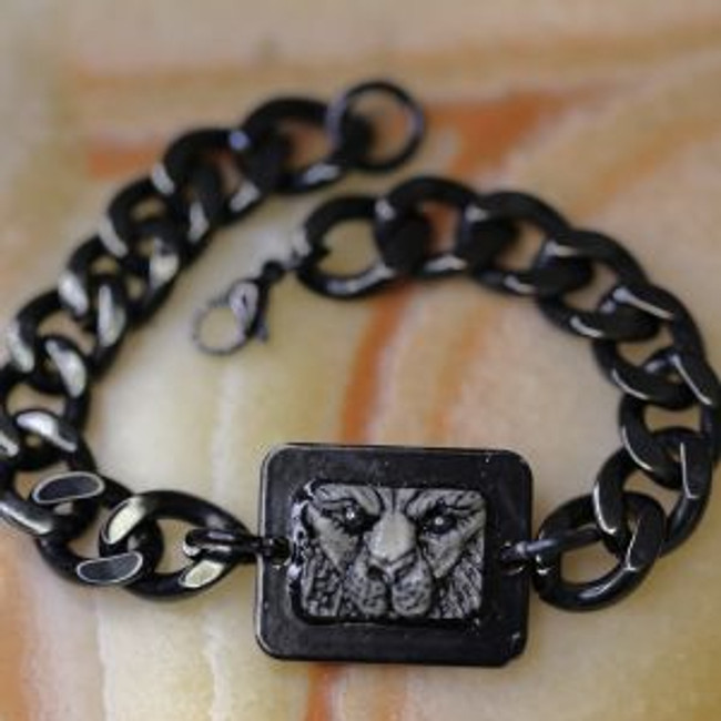Paul Grussenmeyer carved big cat face with hematite eyes on American moose antler/stag mounted in a powder-coated aluminum frame with blackened stainless steel mens Cuban Chain bracelet.  Excellent for casual daily wear.