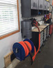 Hose reel attached to wall in a garage.