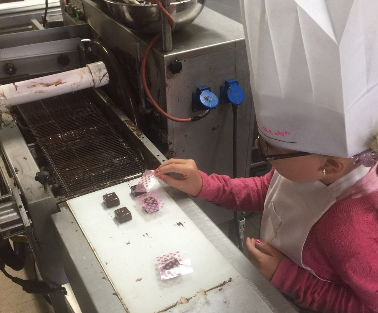 Decorating the chocolates that comes out from the enrobing machine.
