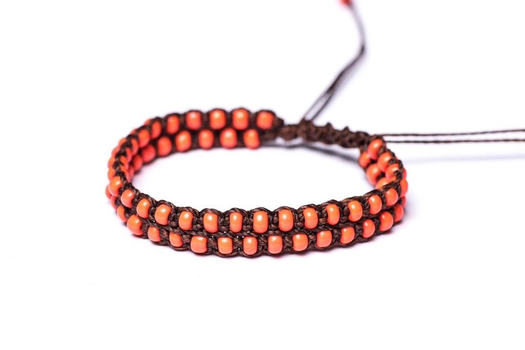 Beautifully handwoven bohemain chic braided dark brown silk thread bracelet with fiery coral seed beads. One size, adjustable cord.