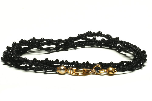 "32"" braided black silk thread necklace with black seed beads and gold plated clasp. Skillfully handmade by artisans for a bold bohemian look and richly plated in gold to adorn your beauty."
