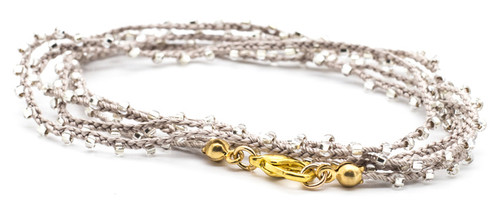 "32"" braided beige silk thread necklace with clear seed beads and gold plated clasp."