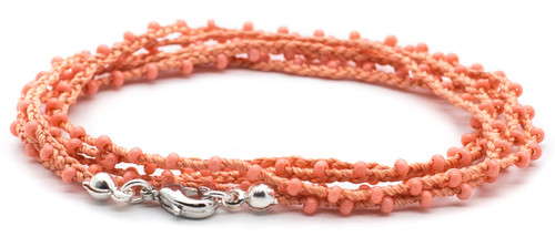 "32"" braided coral silk thread necklace with coral seed beads and silver plated clasp."