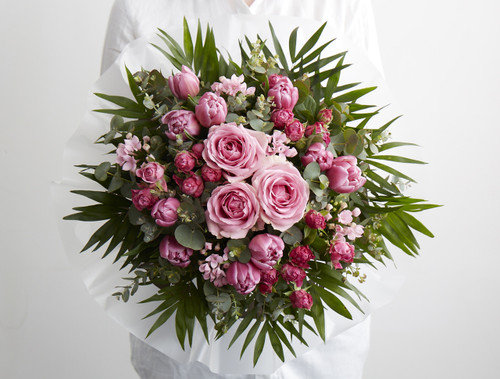 The perfectly pink bouquet for Spring. Seasonal spring-time blooms including tulips are gathered together in little clusters surrounding a heart of roses giving a kaleidoscope of ruby and pink tones.