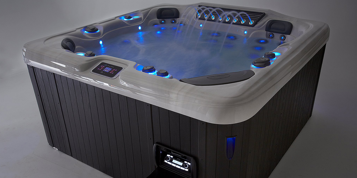 Image of a Dynasty Spa with water illuminated with blue l.e.d. lights on show room floor
