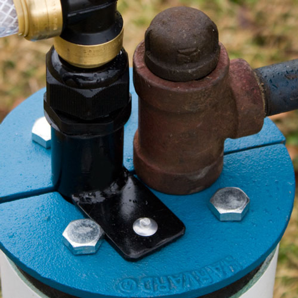 "The EarthStraw Mounting Bracket is shown here mounted to a cast iron split well seal. It connects to any flat surface with a 7/8"" diameter (or larger) opening for EarthStraw (which may be drilled). It comes with a drill and hammer-rivets for securing to the surface but may also be attached with 1/4-20 nut and bolt."