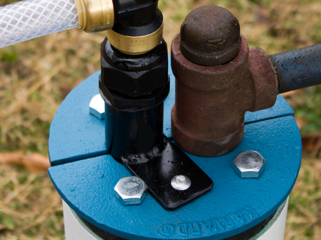 Installation shown with Mounting Bracket attached to an existing cast iron well seal.