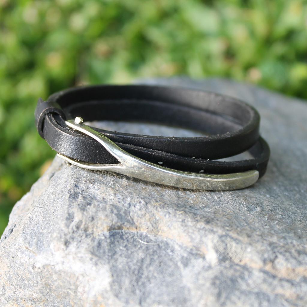 Silver bronze closure on black leather wrap bracelet