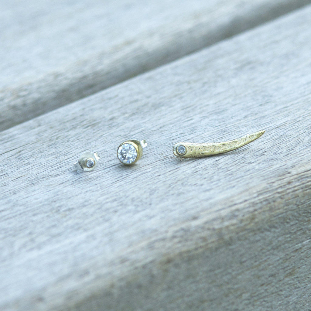 set of three (ear pin and two studs to mismatch) in brass with white stone