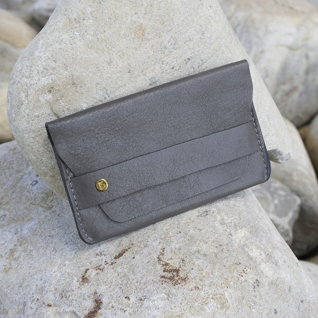 grey leather card case with 'take more detours' brass plate
