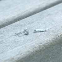 set of three (ear pin and two studs to mismatch) in silver with white stone