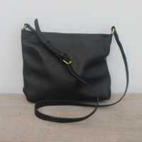 black leather handbag with top zipper and adjustable straps