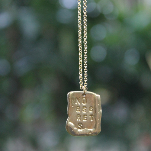 "Long necklace in gold features ""NO REGRETS"" inspirational message"