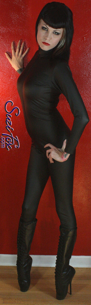 """Custom Catsuit by Suzi Fox shown in Matte Black (no shine) Vinyl/PVC coated Nylon Spandex. Shown with optional 1-slider crotch zipper. Perfect for DKR Catwoman Costume. You can order this Catsuit in almost any fabric on this site.  • Available in black matte (no shine), white matte (no shine), and gloss black, red, white, light pink, neon pink, fuchsia, purple, royal blue, navy blue, turquoise, stretch vinyl coated spandex. • Your choice of front or back zipper (front zipper shown). • Optional 1 or 2-slider crotch zipper, and """"Selene"""" from Underworld TS zipper, or aluminum circular slider zipper like Catwoman comic characters. • Optional wrist zippers • Optional ankle zippers • Optional finger loops • Optional rear patch pockets • Made in the U.S.A."""