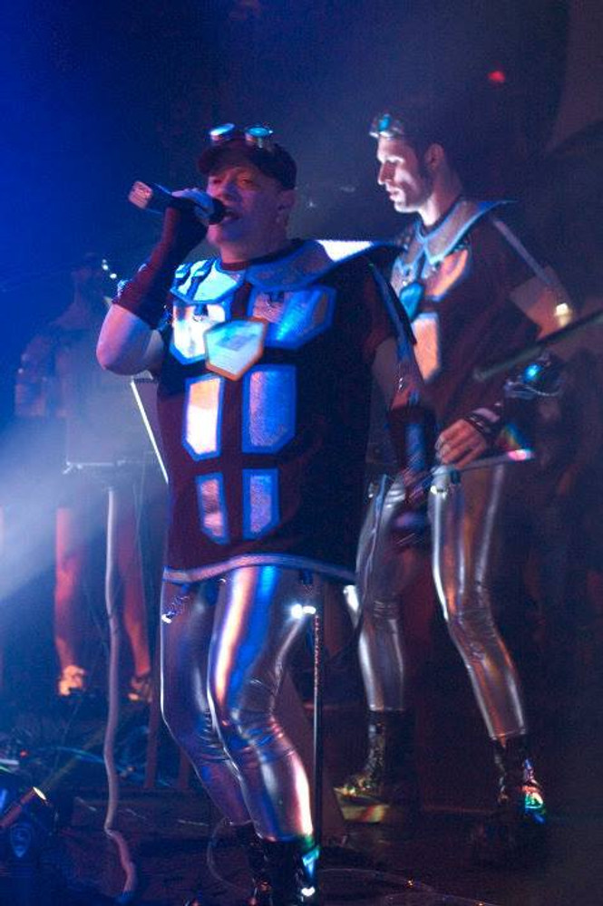 Customer photo! The upbeat vocal dance/pop music of Oscillator X draws from a variety of progressive electronic styles to create a unique new sound that is listenable as well as danceable. John Mendenhall and Kyle Ward pump it up in their Suzi Fox silver pants.