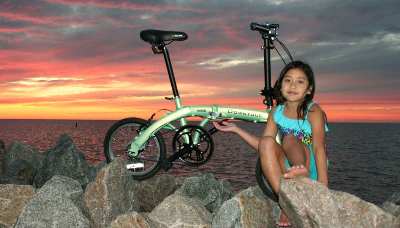 mini folding bike during sunset with little girl