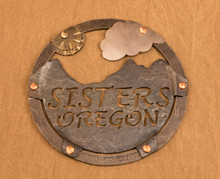 iron trivet with Three Sisters mountains, sun and single small cloud, multiple metals