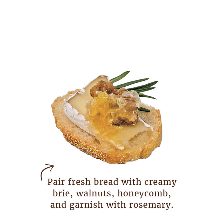 Pair fresh bread with cream brie, walnuts, honeycomb, and garnish with rosemary.