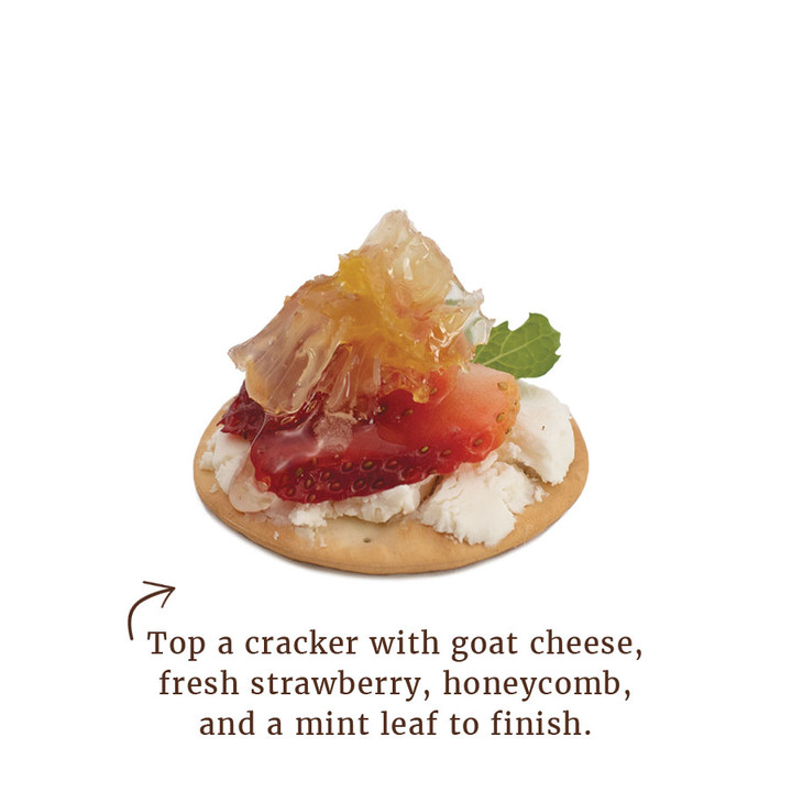 Top a cracker with goat cheese, fresh strawberry, honeycomb, and a mint leaf to finish.