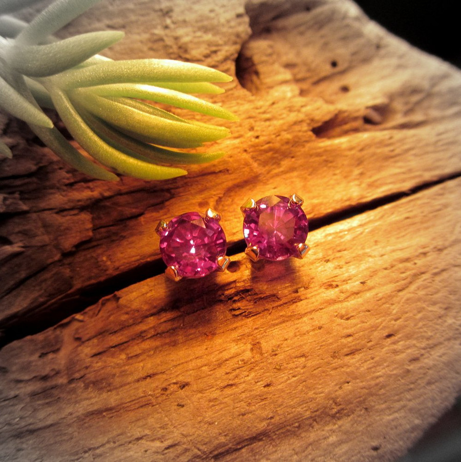 Lab grown real Alexandrite stud earrings under incandescent light