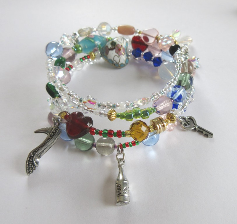 View of the La Boheme Opera Bracelet featuring Musetta's shoe, the bohemian's wine and mimi's key.