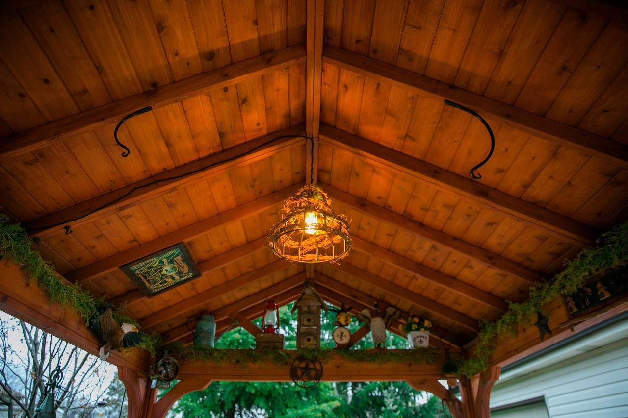 """1"""" x 6"""" red cedar tongue and groove roof panels illuminated in the evening / 2"""" x 4"""" rafters / 4"""" x 4"""" ridge beam / 14' x 10' Gabled Roof Pavilion, Western Red Cedar, Burbank, IL"""