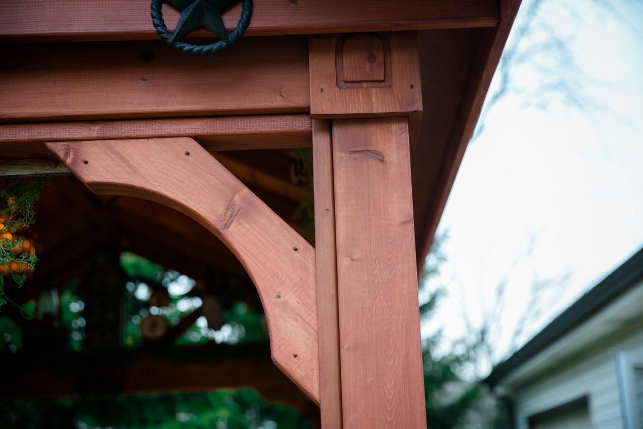 "Close up of half moon corner braces, beam, and square décor motif atop 5"" square posts"