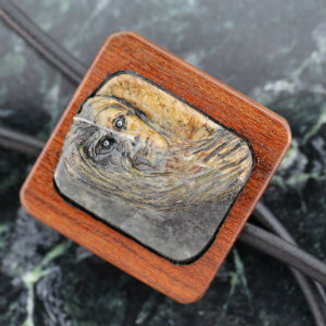 Good & Evil Face carved on Picasso marble. Mounted on Tigerwood. Leather cord. Tigerwood tips with hematite ends.