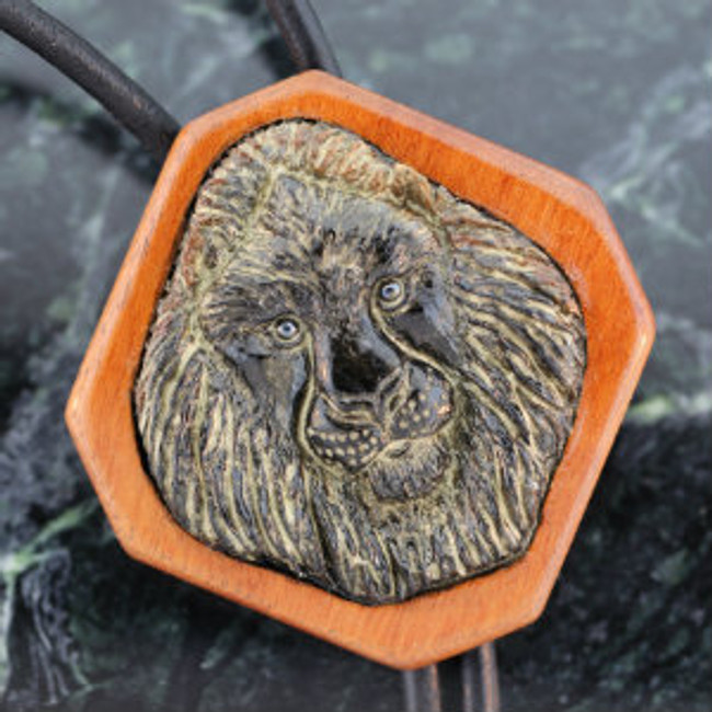 Bolo. Black African Lion carved on Picasso Marble. Mounted on Tigerwood. Leather cord. Hematite eyes. Ipe wood tips with hematite ends.