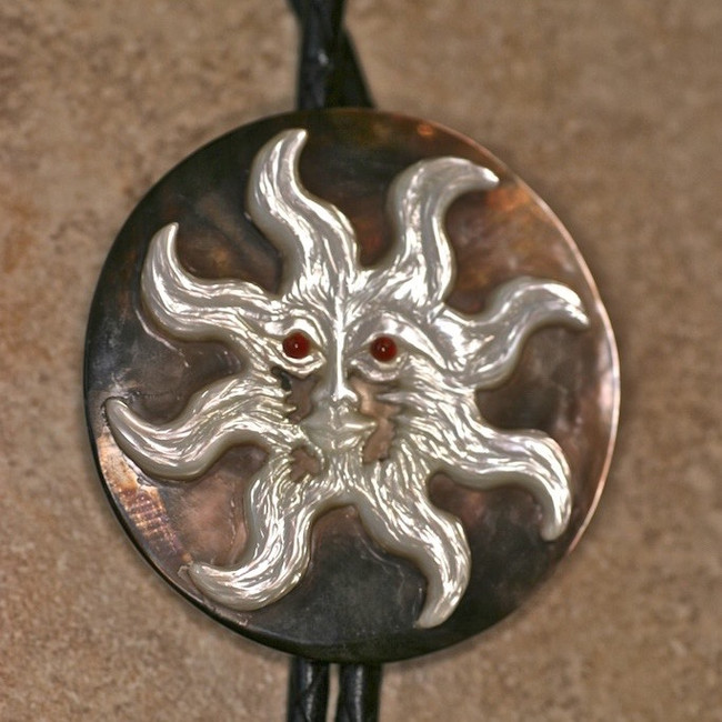 "Bolo. ""Old Sol"" is a white pearl carving mounted on black pearl. Leather cord. Natural claw tips."
