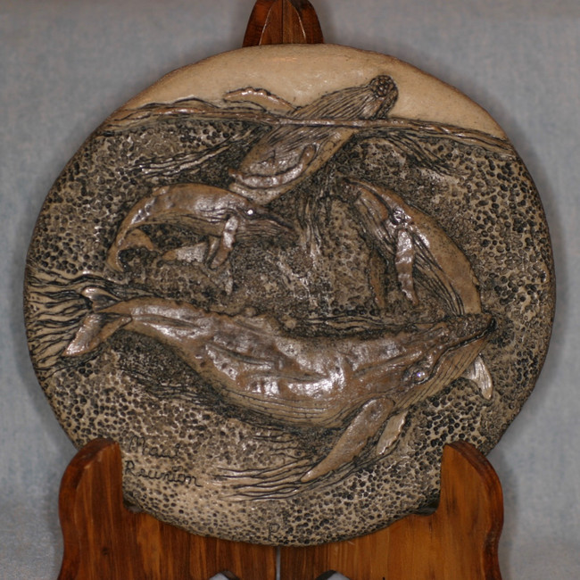 """Maui Reunion""  Humpback whale family carved on a 6.5"" diameter fossil whale intervertebral disc. For home or office display."