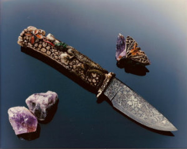 """""""Butterfly Hunter"""". A fully carved India Sambar stag handle on a forged damascus knife by Master bladesmith, Hank Knickmeyer. This knife features a lizard crawling over rocks with its tongue extended in pusuit of a butterfly meal. Ruby eyes, 4.13"""" mosaic (butterflies, flowers, spiderwebs, and HK's) damascus blade, twist pattern edge, carved cast bronze guard, 9.38"""" overall length. With a nice display stand."""
