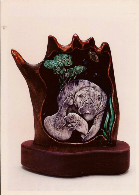 """""""Save My Baby"""". A mother manatee and calf sculpture carved on American moose antler palm section by Paul Grussenmeyer. Garnet eyes. Heavy walnut base. 8"""" X 10""""."""