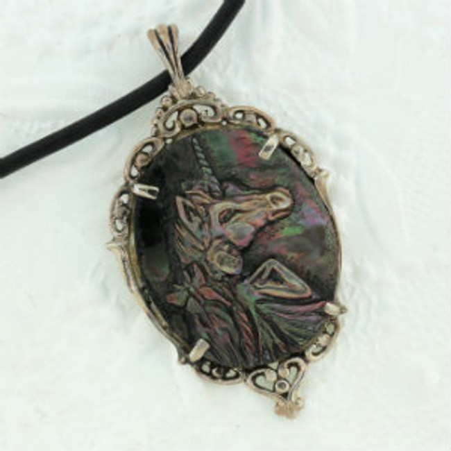 """A fairy with unicorn and butterfly carved on black pearl by Paul Grussenmeyer. Set in an antiqued sterling silver frame. 16.5"""" Greek leather cord."""
