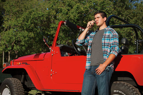 Man standing next to red Jeep using two-way radio