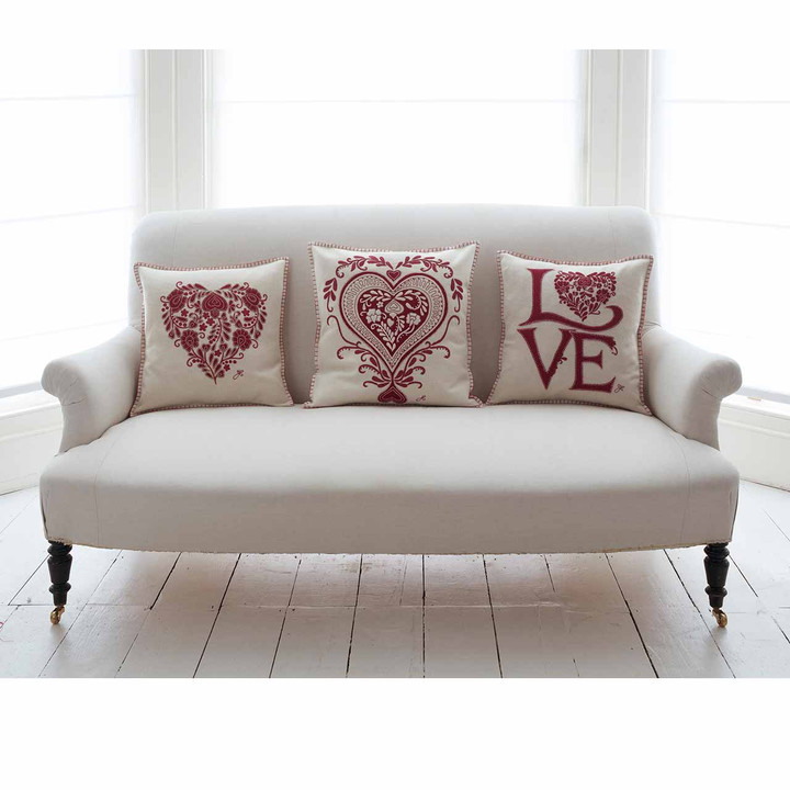 Cream luxury Romany Love cushion with hand embroidered appliqué red letters and stitched heart motif.