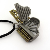 grand piano locket open to show keyframe and soundboard